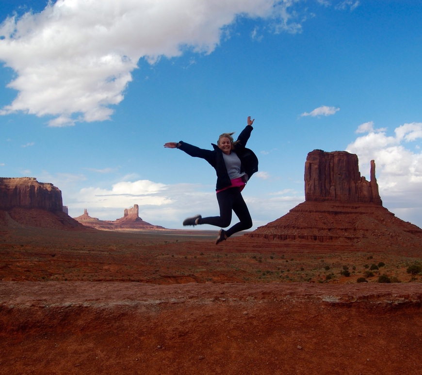 A girl jumps in Monument Valley, Utah with butes behind her