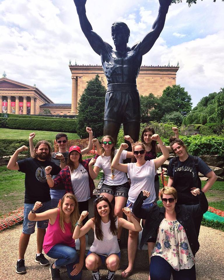 Fists pumped as a group poses next to the Rocky statue, Philadelphia